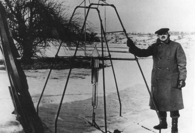 "Robert H. Goddard, bundled against the cold weather of March 16, 1926, holds the launching frame of his most notable invention — the first liquid-fueled rocket, an example of a ""P-type"" loonshot."
